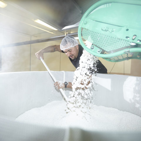 Brewer stirring rice as it comes off the conveyor belt