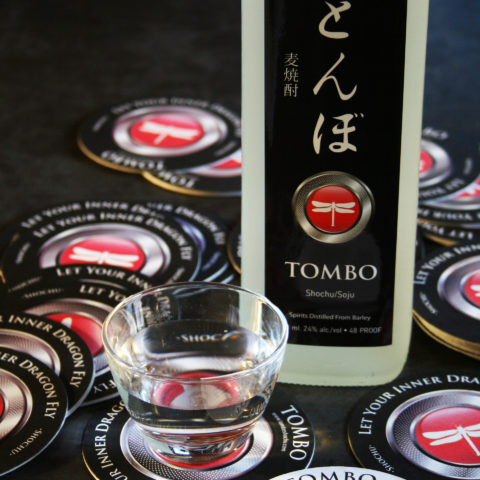 Glass of Tombo next to a bottle of Tombo with Tombo Coasters