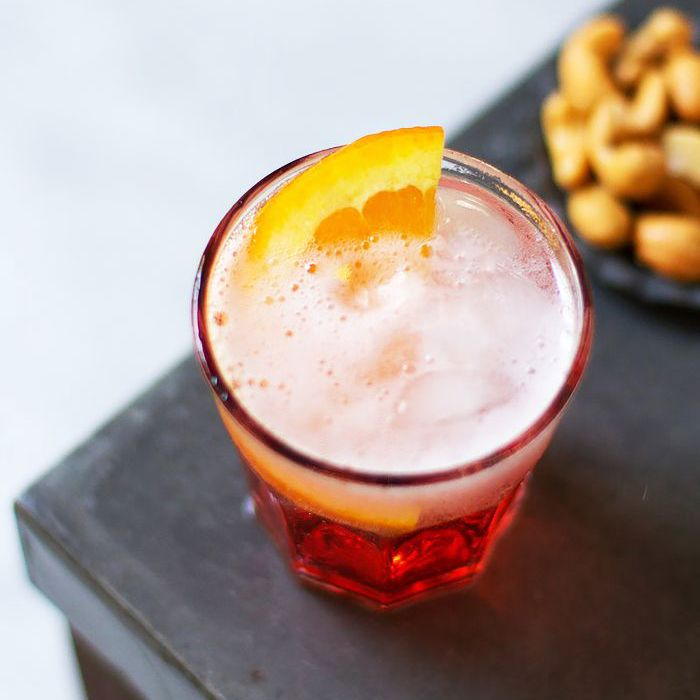 nigori negroni cocktail in a glass on a wooden table