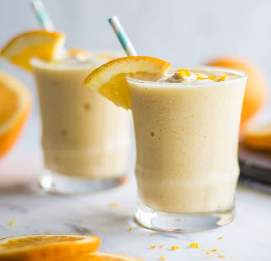 Orange coco smoothie with orange slices on a marble table