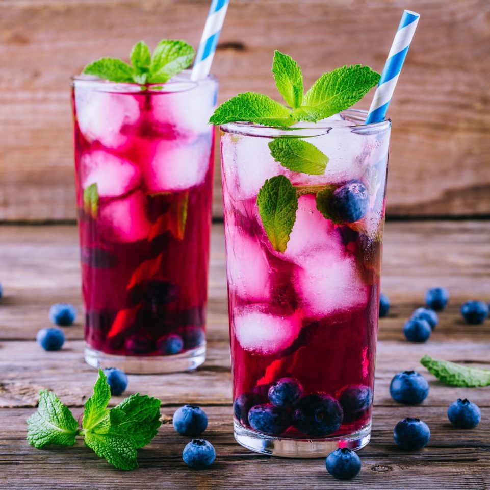 Blueberry ice sangria with mint in glasses on wooden table