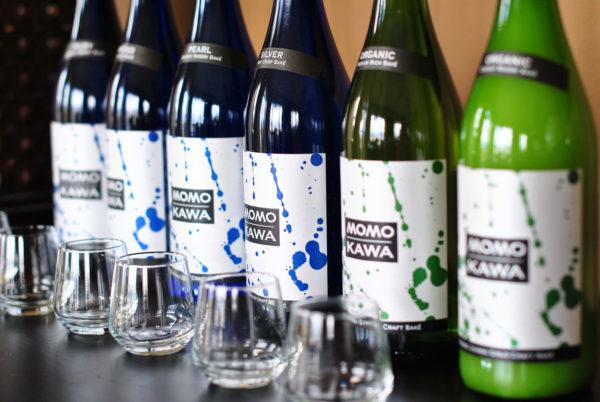 bottles for Momokawa and saké glasses in front at a saké blending event